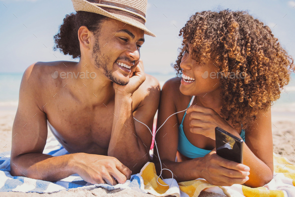 Couple on beach listening to music and smiling - Stock Photo - Images