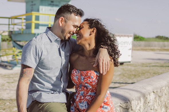 Happy multiracial couple on seafront - Stock Photo - Images
