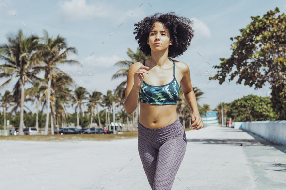 Black fit girl jogging on tropical waterfront - Stock Photo - Images