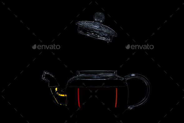 Transparent teapot with black tea on a black background - Stock Photo - Images