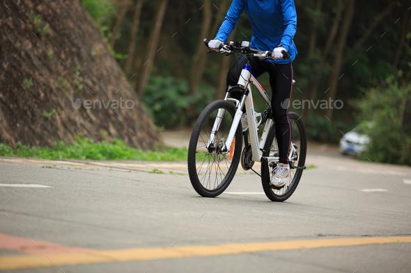 Riding mountain bike climbing slope on road - Stock Photo - Images