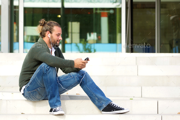 Young man sitting on steps listening to music with cell phone - Stock Photo - Images