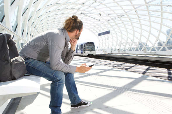 Man waiting for train arriving at station - Stock Photo - Images