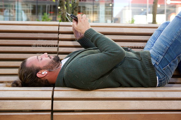 Man lying down on bench with earphones - Stock Photo - Images