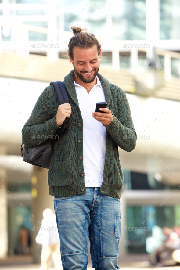 Smiling man with beard looking down at cellphone - Stock Photo - Images