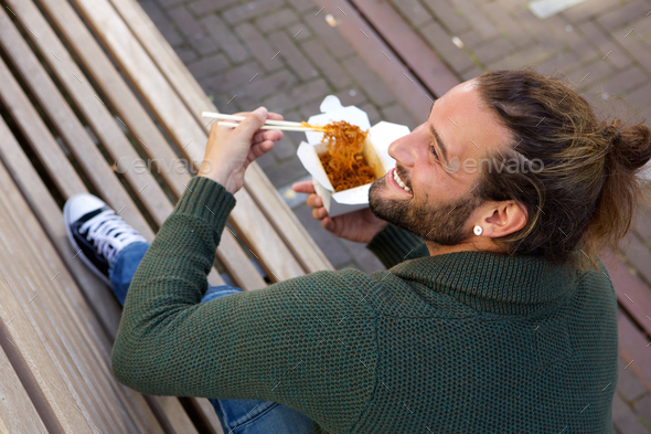 Smiling man eating chinese food on bench - Stock Photo - Images
