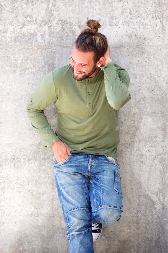 Young man leaning against wall with hand in hair - Stock Photo - Images