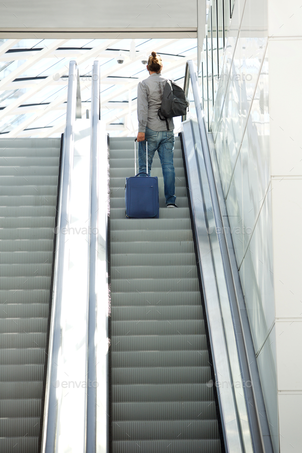 Man standing on escalator with travel bags - Stock Photo - Images