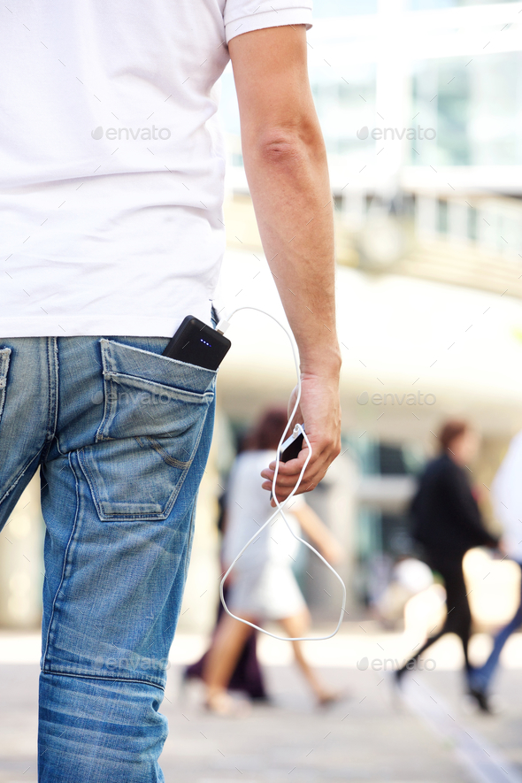 Holding cellphone with battery charger in pocket - Stock Photo - Images