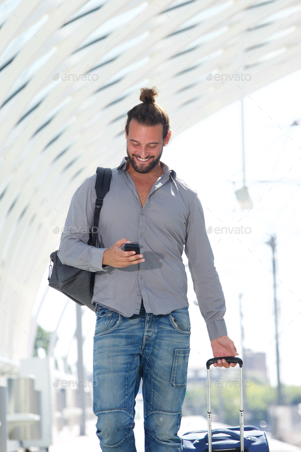 Handsome man walking with mobile phone with suitcase - Stock Photo - Images