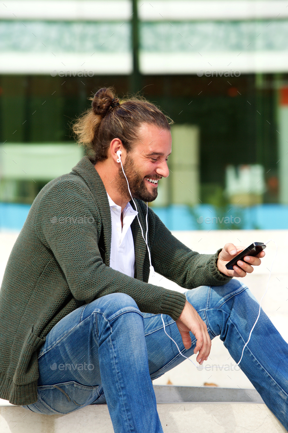 Smiling man sitting on steps listening to music with smart phone - Stock Photo - Images