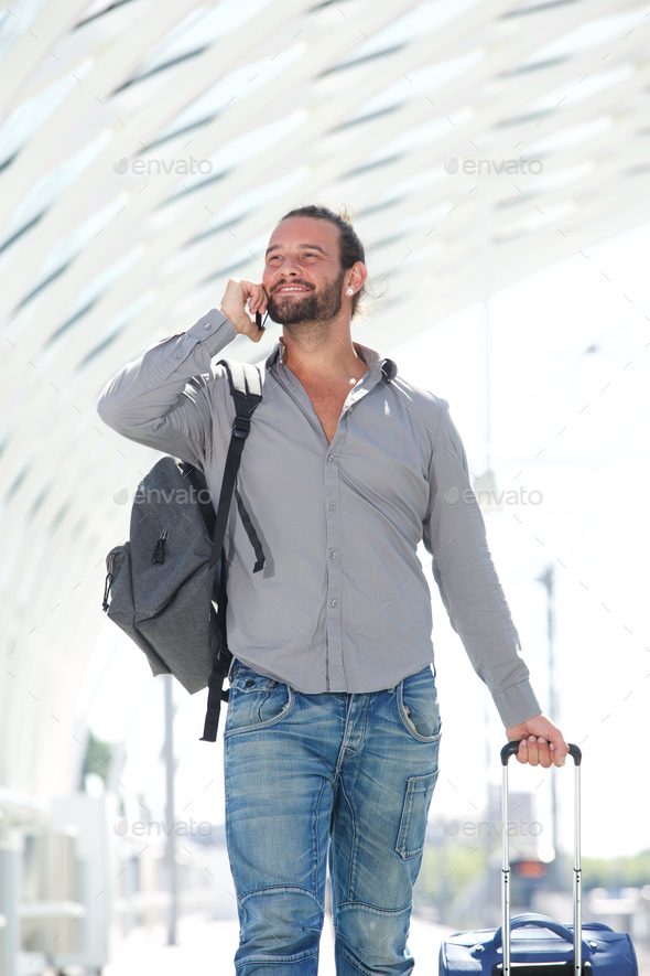 Handsome man walking with mobile phone and luggage - Stock Photo - Images