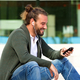 Smiling man sitting on steps listening to music with smart phone - PhotoDune Item for Sale