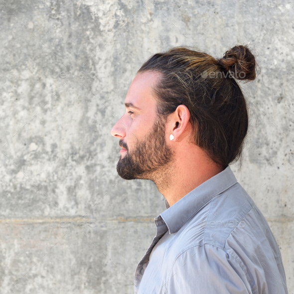 Side portrait of serious man with beard and hair bun - Stock Photo - Images