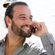 Smiling man with beard talking on phone at station - PhotoDune Item for Sale