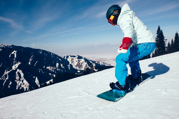 Snowboarder descent on alpine mountain slope - Stock Photo - Images