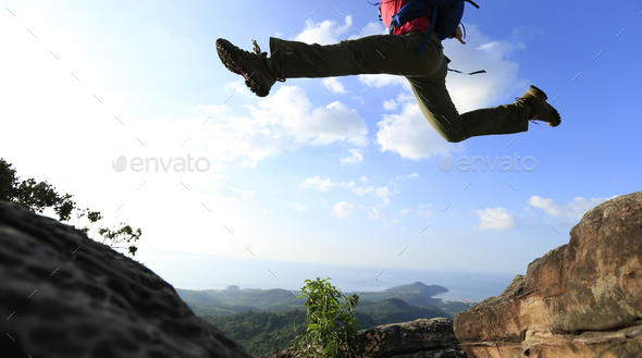 Jumping over precipice between two rocky mountains  - Stock Photo - Images