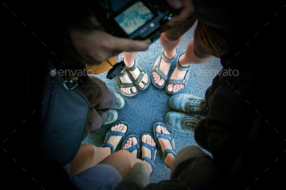 Top view of friends legs and feet in sandals and boots standing in circle on asphalt road - Stock Photo - Images