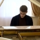 Young Pianist with Glasses Playing on a White Grand Piano - VideoHive Item for Sale