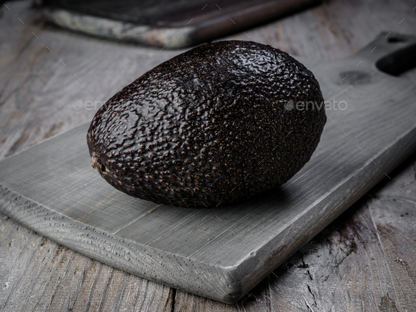 Whole black kiwi in rustic wood - Stock Photo - Images