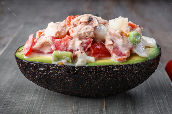 black kiwi open in half stuffed with salad on rustic wood - Stock Photo - Images