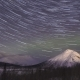 Night Starry Sky with Star Trails and Green Northern Lights in Snowy Mountains at Winter Night - VideoHive Item for Sale