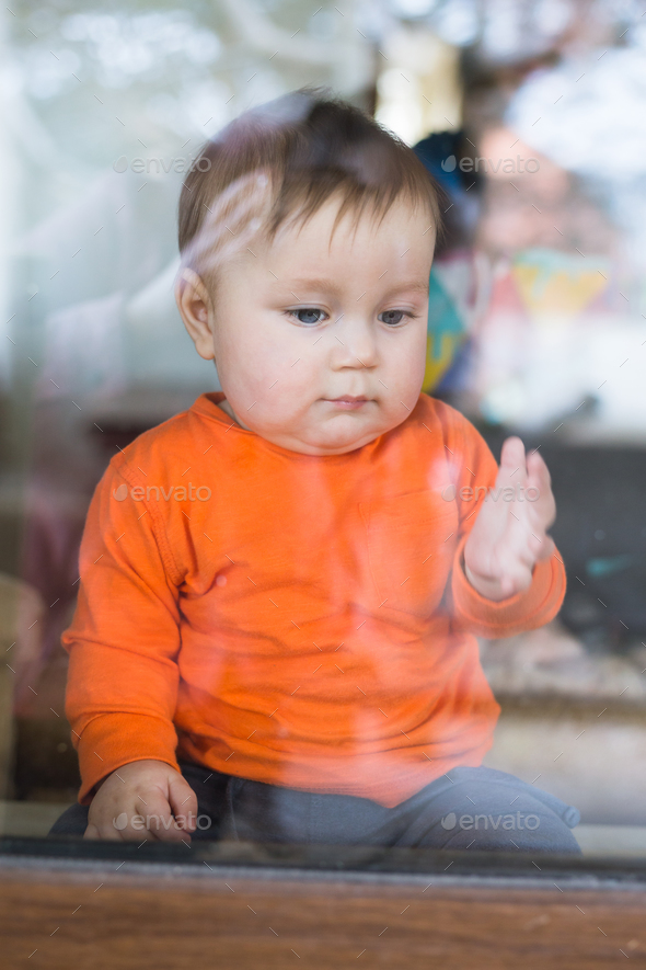 A cute little boy is sitting on the windowsill outside the window - Stock Photo - Images