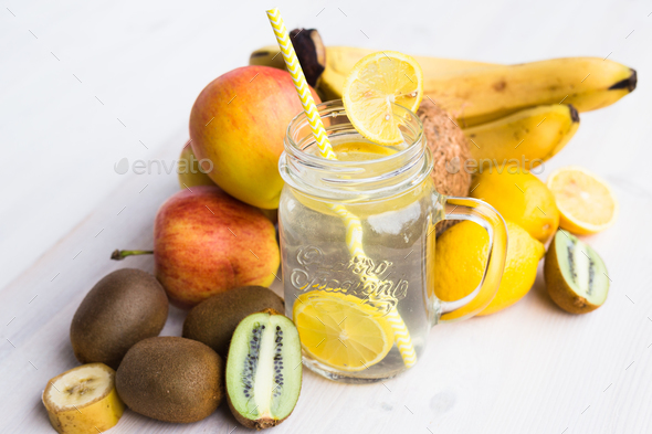 Glass of fresh lemonade in an environment of fruits - Stock Photo - Images