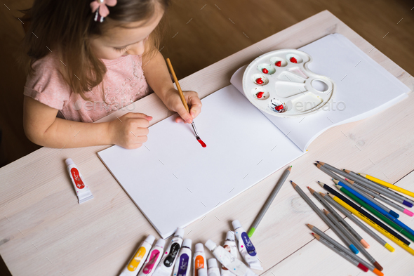 Cute little girl painting picture on home interior background - Stock Photo - Images