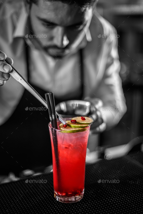 Bartender decorating non-alcoholic pomegranate cocktail - Stock Photo - Images