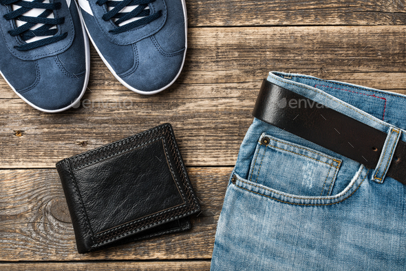 Blue Jeans with belt, shoes and leather wallet on wooden background - Stock Photo - Images