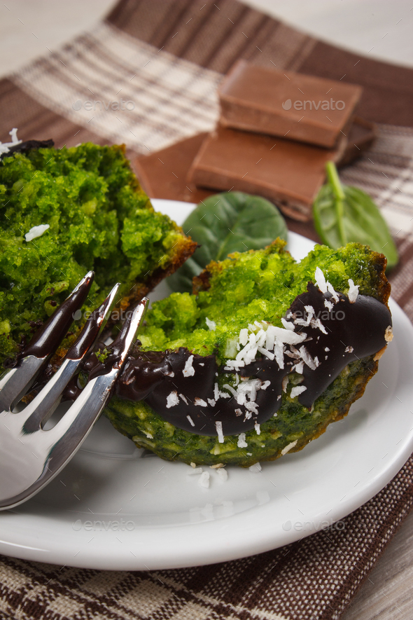 Fresh muffins with spinach, desiccated coconut and chocolate glaze - Stock Photo - Images