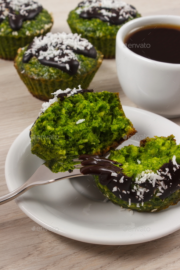 Fresh muffins with spinach, desiccated coconut, chocolate glaze and cup of coffee - Stock Photo - Images