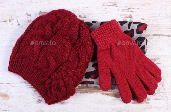 Pair of woolen gloves, cap and shawl for woman on old board - Stock Photo - Images