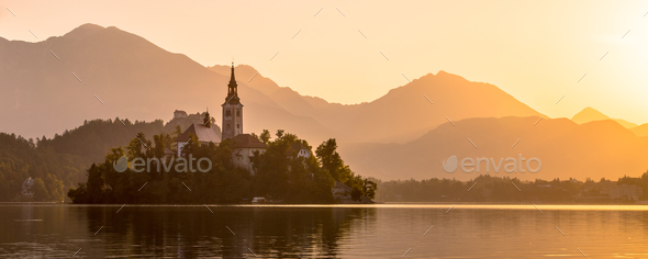 Island in lake Bled with orange Julian Alps sillhouette - Stock Photo - Images