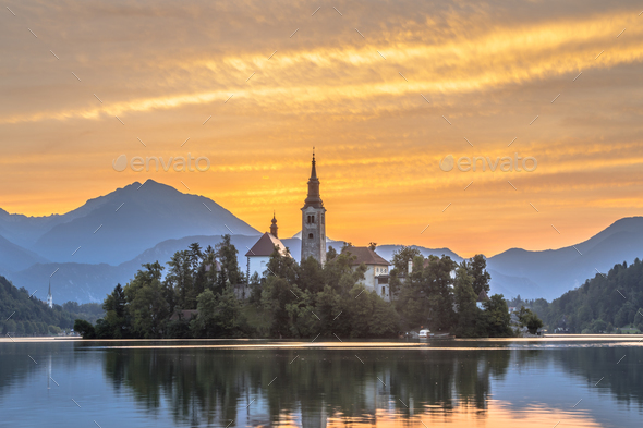 Famous Lake bled with church under orange morning sky - Stock Photo - Images