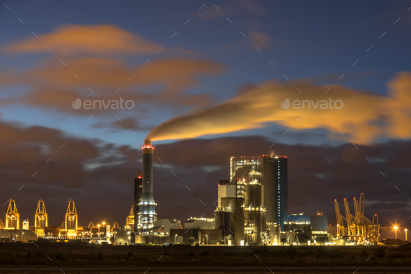 Industrial landscape with illuminated clouds at night - Stock Photo - Images