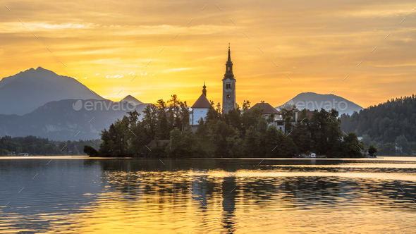 Famous Island in Lake bled with church under orange morning sky - Stock Photo - Images