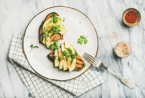 Flat-lay of avocado toast on plate and seasoning , top view - Stock Photo - Images