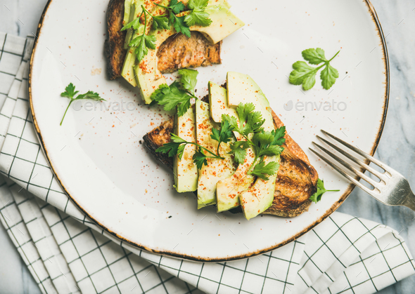 Flat-lay of avocado toast on plate, top view - Stock Photo - Images