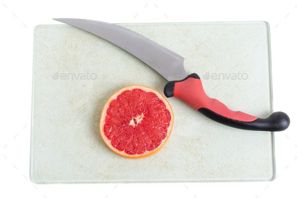 Sliced grapefruit and knife on platter. - Stock Photo - Images