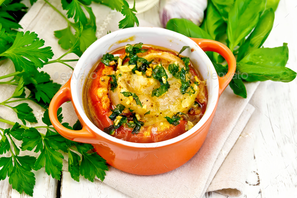 Fish baked with tomato in red pot on towel - Stock Photo - Images