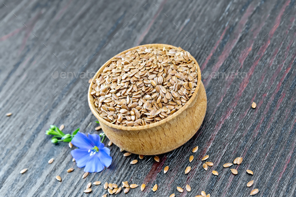 Flaxen brown seed in bowl with flower on board - Stock Photo - Images