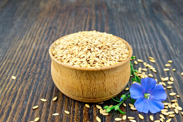 Flaxen white seed in bowl with flower on board - Stock Photo - Images