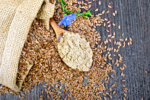 Flour flax in spoon with flower on board top - Stock Photo - Images