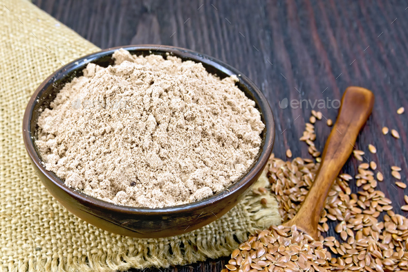 Flour linen in bowl with seeds in spoon on sacking - Stock Photo - Images
