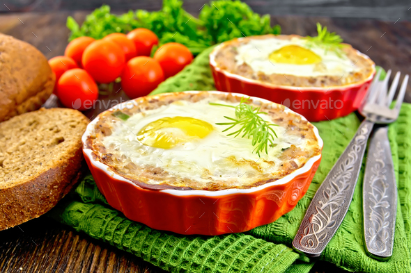 Tartlet meat with egg in pan on board - Stock Photo - Images