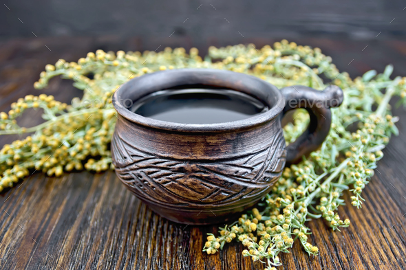 Tea with wormwood in cup on board - Stock Photo - Images