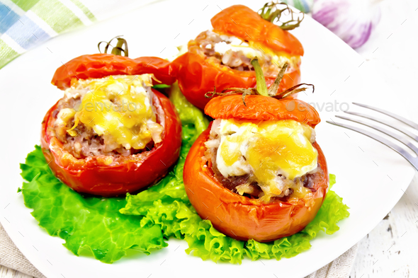 Tomatoes stuffed with meat and rice with lettuce in plate on board - Stock Photo - Images