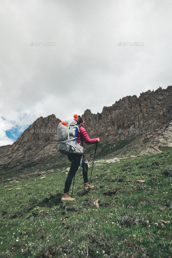 Backpacking woman ascent on high altitude mountains - Stock Photo - Images